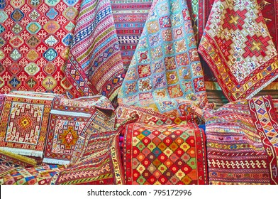The complex geometric, floral, stellar and other patterns on colored woven carpets in stall of Vakil Bazaar, Shiraz, Iran.