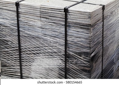 complex granite slabs packed in foil on a wooden pallet, note shallow depth of field