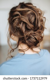 Complex hairstyle on the head of a brown-haired woman, rear view close-up. Fashionable professional women's hairstyle.