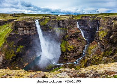 Complex of high waterfalls of Haifoss in a dangerous tundra canyon. Cloudy and windy summer day in Iceland. The concept of extreme and phototourism