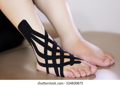 complex kinesio taping on the right ankle of a white skin  woman