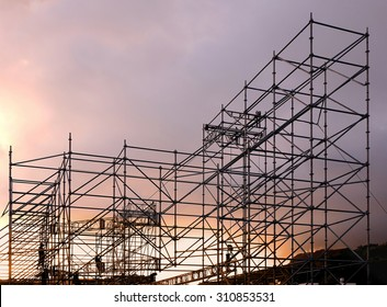A complex scaffold setup for a stage for an outdoor concert seen at sunset