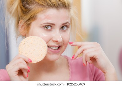 Complexion, skincare products concept. Woman having wash gel on face holding sponge about to clean her skin.