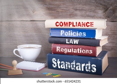 Compliance concept. Stack of books on wooden desk