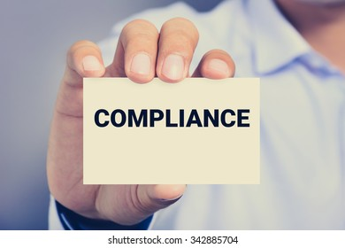 COMPLIANCE word on the card shown by a man
