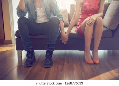 Complicated couple holding hands sitting on couch after quarrel fight thinking of break up or divorce, black upset man and woman not talking having conflict, bad relationships concept.