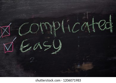 Complicated or Easy written with color chalk concept on the blackboard