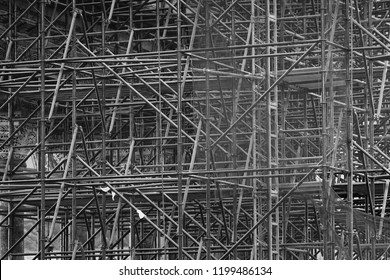 Complicated scaffolding consisting of many poles and struts inside a historic building, black and white.