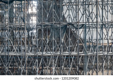 Complicated scaffolding consisting of many poles and struts inside a historic building.