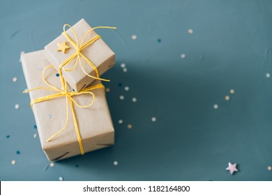compliment gifts. holiday celebration and greeting tradition concept. two small presents wrapped in craft paper on blue background decorated with festive confetti.