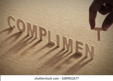 COMPLIMENT wood word on compressed or corkboard with human's finger at T letter.