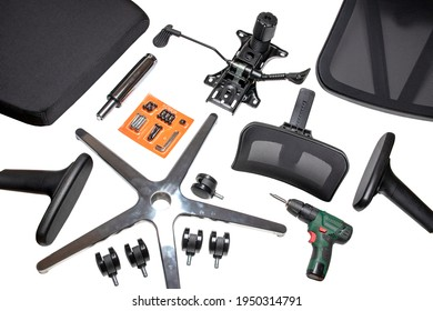 Components of an office chair. Closeup of a complete set of spare parts for assembly of an computer or office chair and a cordless drill for the construction isolated on a white background.