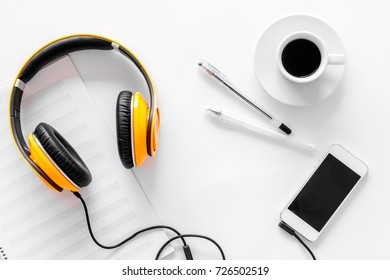 Compose music. Headphones, music notes, phone and coffee on white background top view
