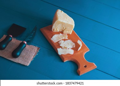 Composed cloesup detail view of aged cheddar cheese with cheese knife set, over vintage blue wooden backdrop
