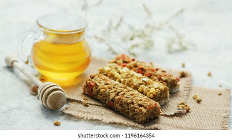 Composed few cereal bars on canvas napkins with glass jar of golden honey near