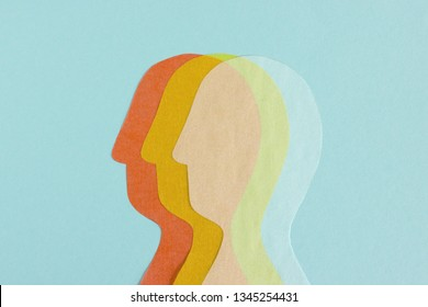 Composed row of three transparent paper cutout of heads overlapped on blue background