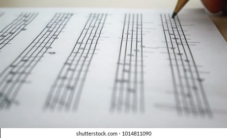 Composer Comes Down a Song and Records Musical Notes Of Melody On A Paper Leaf by Pensil