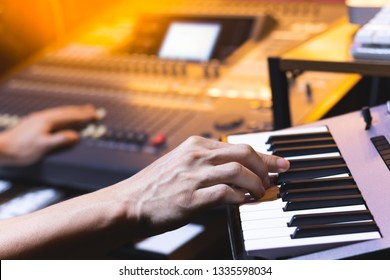 composer, producer hands playing keyboard for recording midi track in home studio. music production concept