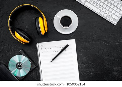 Composer and song writer desktop with headphones and notes on black background top view mock up