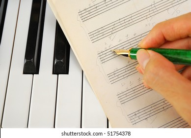 Composing music and writing on old music score on a black and white piano keyboard. For concepts like music and creativity.