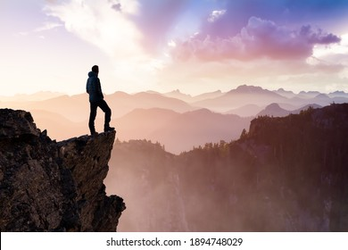 Composite. Adventurous Man Hiker With Hands Up on top of a Steep Rocky Cliff. Sunset or Sunrise. Landscape Taken from British Columbia, Canada. Concept: Adventure, Explore, Hike, Lifestyle