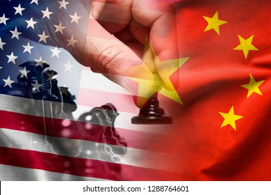 Composite of the Chinese and American flags with the hand of a chess player moving a pawn in a concept of politics, planning, strategy and discussion