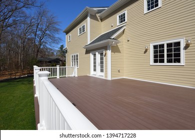 Composite deck in house backyard. Brown boards, white railing posts and veranda. Large, spacious, new construction.