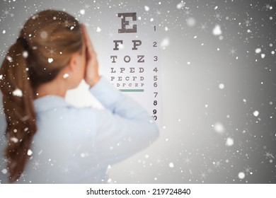 Composite image of brunette woman making an eye test against snow falling