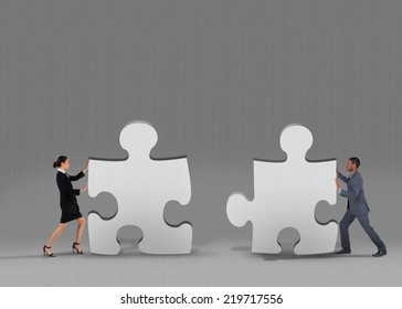 Composite image of business team standing and pushing against grey jigsaw pieces