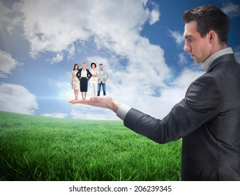 Composite image of businessman holding business team against green field under blue sky