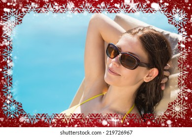 Composite image of cheerful woman by swimming pool against snow