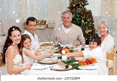 Composite image of Children pulling a Christmas cracker at home against snow falling