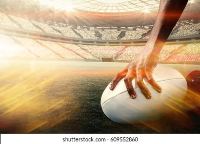Composite image of cropped image of athlete holding rugby ball against ball of fire 3d