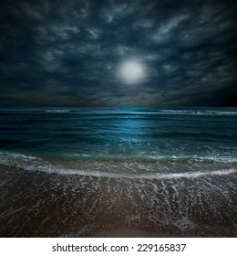 A composite image depicting the full moon rising behind clouds at night over a tranquil beach with waves lapping onto the sand.