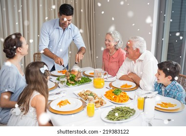 Composite image of Extended family at dining table in house against snow falling