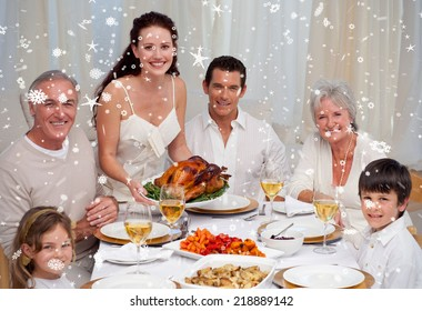 Composite image of Family eating turkey in a dinner against snow falling