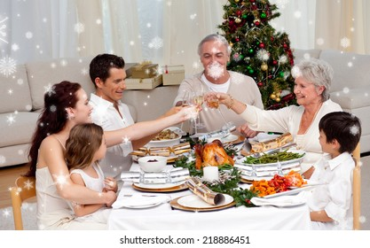 Composite image of Family toasting in a Christmas dinner against snow falling