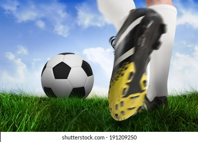 Composite image of football boot kicking ball against field of grass under blue sky