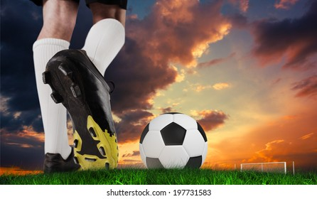 Composite image of football boot kicking ball against green grass under dark blue and orange sky