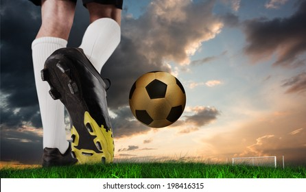 Composite image of football boot kicking gold ball against green grass under blue and orange sky