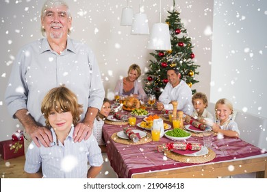 Composite image of Grandfather and grandson standing beside the dinner table against snow falling