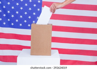 Composite image of hand putting ballot in vote box behind american flag
