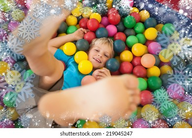 Composite image of happy boy playing in ball pool against snow