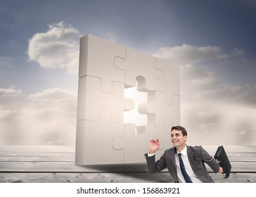 Composite image of joyful businessman holding a suitcase and running in front of incomplete puzzle