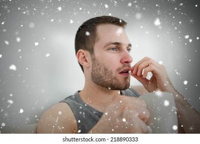 Composite image of man taking a pill against snow falling