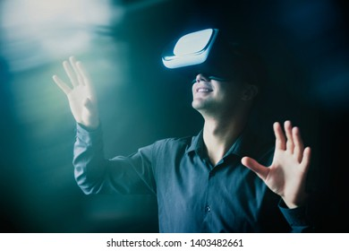 Composite image of a man wearing a VR headset interacting with a simulated virtual reality environment with light flare