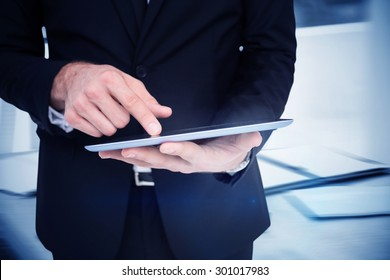 Composite image of mid section of a businessman touching digital tablet