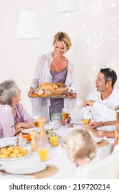 Composite image of mother bringing turkey to dinner table against snow falling