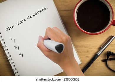 Composite image of new years resolutions against overhead of notepad and pen and coffee
