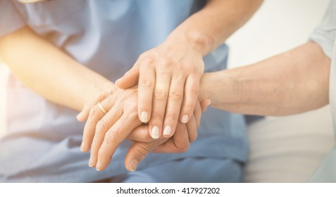 Composite image of nurse holding patient hand on a bed